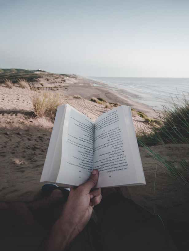 photo of person reading book on beach